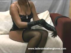 Busty brunette in just sexy basque and stockings enjoys slowly putting on butter soft leather gloves