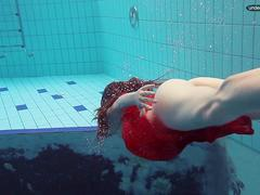 Red Dressed teen swimming with her eyes opened